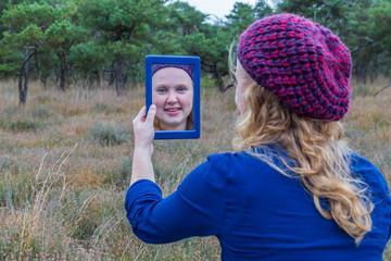 Girl looking in mirror in nature