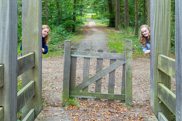 Two girls hiding at entry of hiking trail in nature