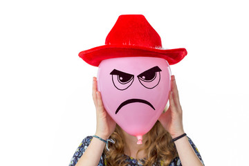 Girl holding pink balloon with angry face and red hat
