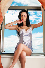 beautiful woman in a chemise sitting on the windowsill