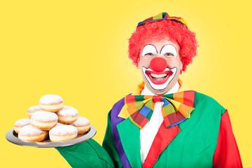 clown mit pfannkuchen vor gelbem hintergrund