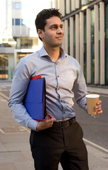 young business man with a coffee holding folders.