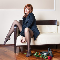 Melancholy young redhead woman portrait while lying on sofa in h