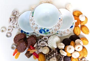 Много печенья и чайный сервиз на белом фоне