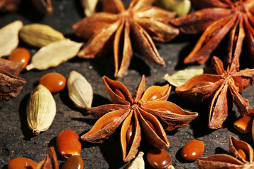 Stars anise and cardamom on wooden background