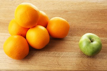 Juicy oranges and green apple on wooden table