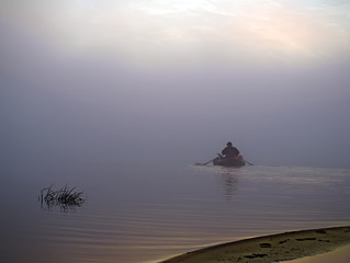 The boat sails away into the fog