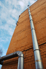 two ventilation pipes on a brick wall