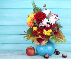 Flower bouquet in blue vase and apple