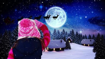 Little girl waving to santa flying over village