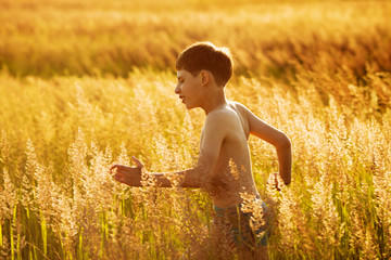 Happy boy running in a field
