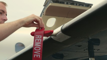 Pilot Attaches Post-Flight Safety Covers Ribbons to Wing