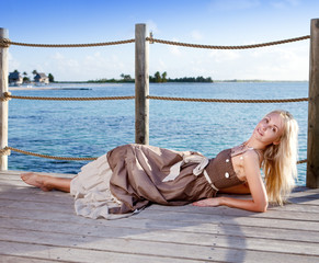 The young beautiful woman  on a wooden platform over  the sea