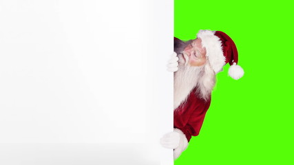 Santa peeking around gift card on green screen background