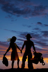 silhouette of woman holding hat back wind cowboy