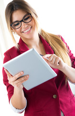 Young smiling woman using digital tablet. Isolated on white.