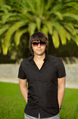 Young handsome man outdoors portrait. Trendy male in sunglasses
