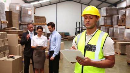 Warehouse managers talking while worker uses tablet pc