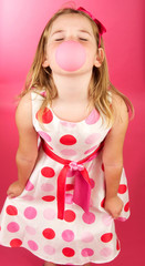 Cute Girl Blowing a Bubble on a Pink Background