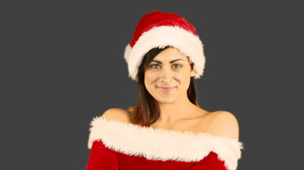 Smiling pretty woman posing in sexy santa outfit