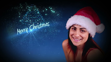 Festive brunette blowing a magical christmas greeting