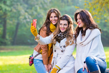 Three beautiful young women in the park taking a photo