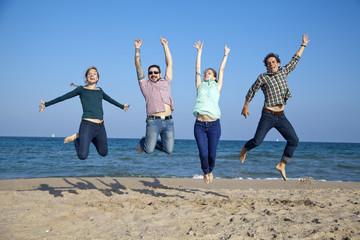 Amigos saltando contentos sobre la arena de la playa