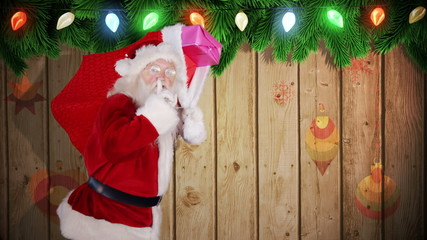 Santa carrying sack of gifts against festive wooden background