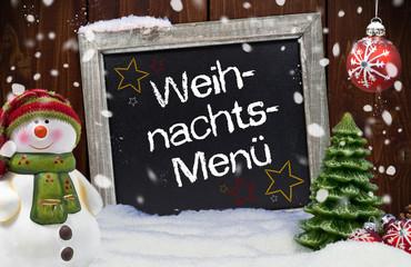 Kreidetafel mit Weihnachtsdekoration und Weihnachtsmenü
