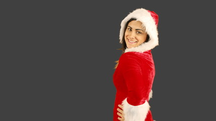 Girl in santa hat blowing over hands and looking at camera