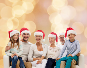 happy family in santa helper hats sitting on couch