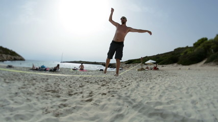 man turns on slackline on empty beach, selective focus