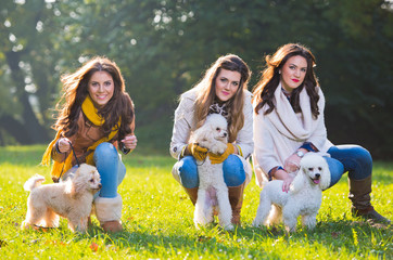 Three young woman with their pet dogs in the park
