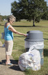 Woman using a rubbish bin to dispose of her garbage