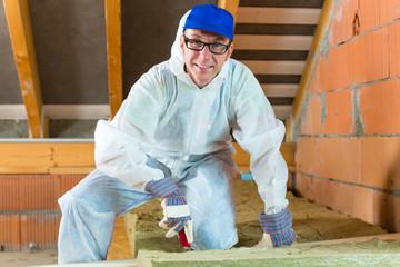 Handwerker schneidet Dämmmaterial für Isolierung
