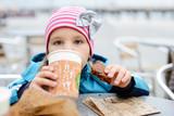 little girl drinking outdoors