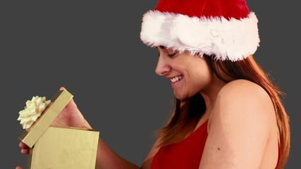 Festive brunette opening a christmas gift