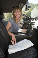 Female driver using map to plan route