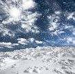 Winter landscape with snow covered hill and blue sky