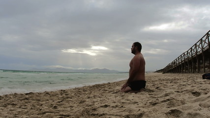 Man meditates on deserted beach Majorca