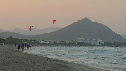 Old couple walk on Muro beach  at sunset kite surfers