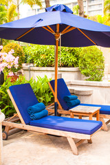 Beach chairs with umbrellas in exotic resort near swimming pool