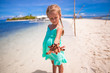 Little adorable girl with starfish in hands at the tropical