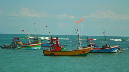 Several small vessels are laid up in a calm bay ocean