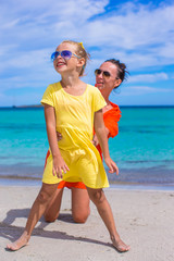 Little girl and young mother having fun on tropical beach