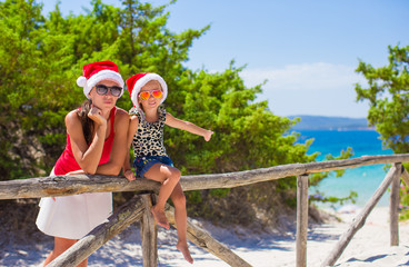 Young mother and little girl in red Christmas hat at tropical