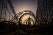 Leinwanddruck Bild - Corkscrew roller coaster at dusk
