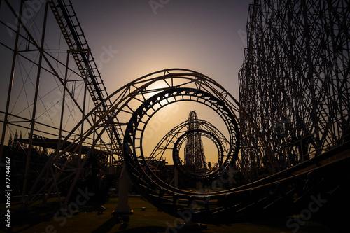 Leinwanddruck Bild Corkscrew roller coaster at dusk
