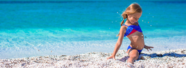 Little girl making leg-split on tropical white sandy beach
