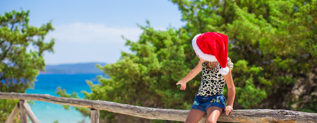 Adorable little girl in christmas hat during summer beach